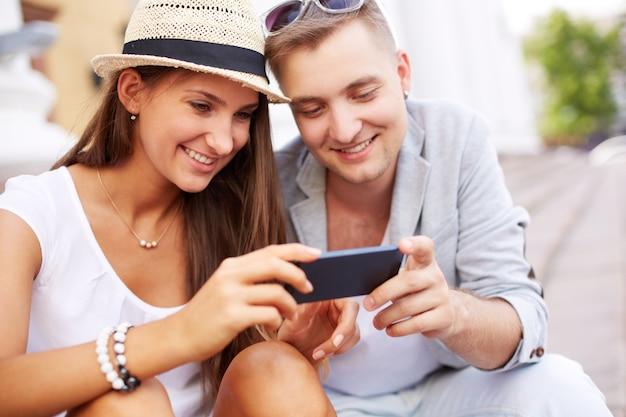 Paare, die an fotos auf mobilen suche