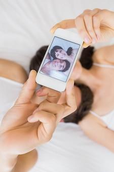 Paare, die auf bett liegen und ein selfie am handy nehmen