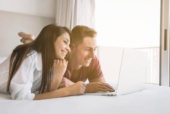 Paare, die auf Bett mit Laptop liegen