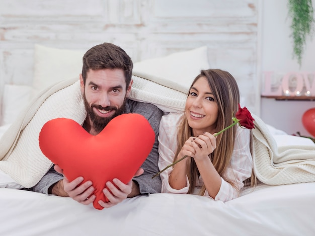 Paare, die auf bett mit weichem rotem herzen liegen