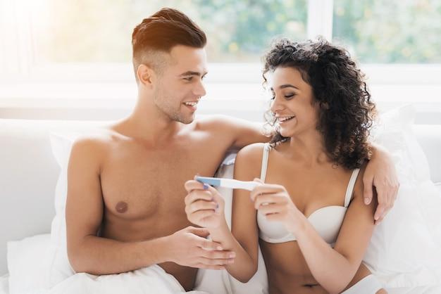 Paare, die auf bett sitzen und schwangerschaftstestmädchen betrachten