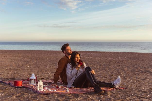 Paare, die auf bettdecke auf sandigem seeufer sitzen