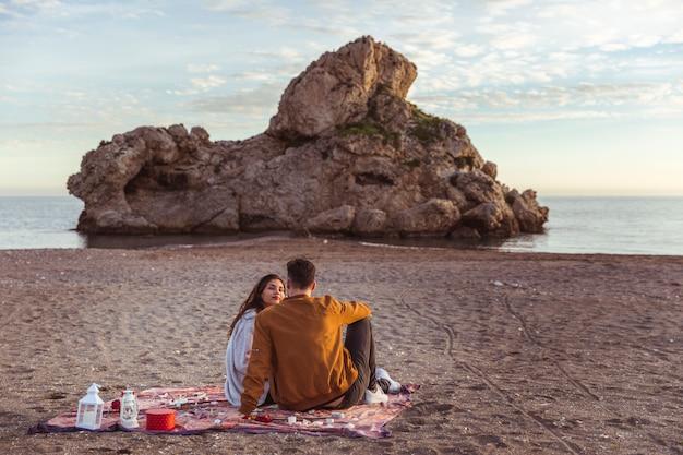 Paare, die auf bettdecke auf seeufer sitzen