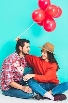 Paare, die auf boden mit ballonen und herzen auf stock sitzen