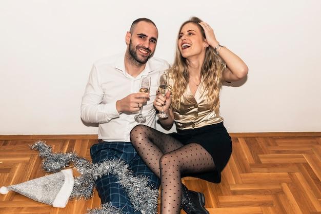 Paare, die auf boden mit champagnergläsern sitzen
