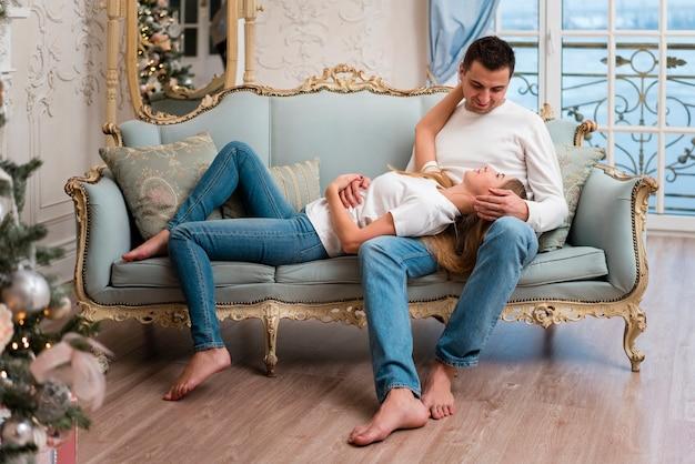 Paare, die auf couch mit christmass baum aufwerfen