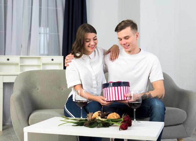 Paare, die auf couch mit geschenkbox sitzen