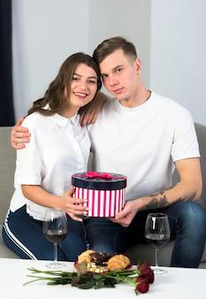 Paare, die auf couch mit großer geschenkbox sitzen