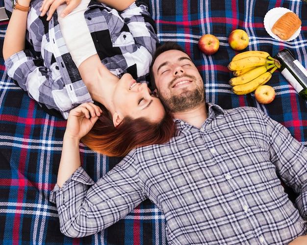 Paare, die auf decke mit vielen früchten schlafen; blätterteig und champagnerflasche