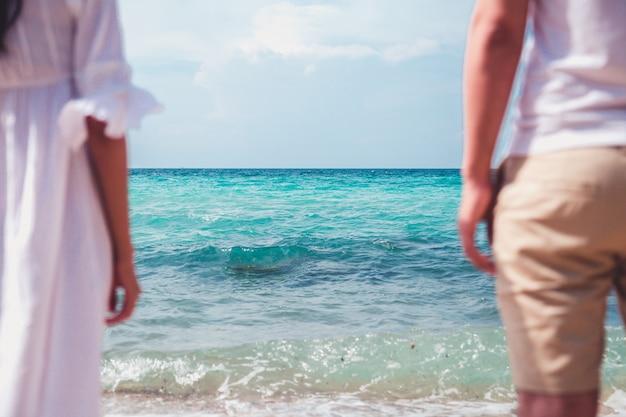 Paare, die auf dem strand mit einem schönen sonnenuntergang im hintergrund küssen.
