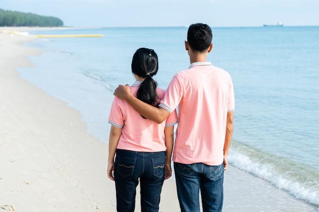 Paare, die auf den strand auf sommerferien gehen
