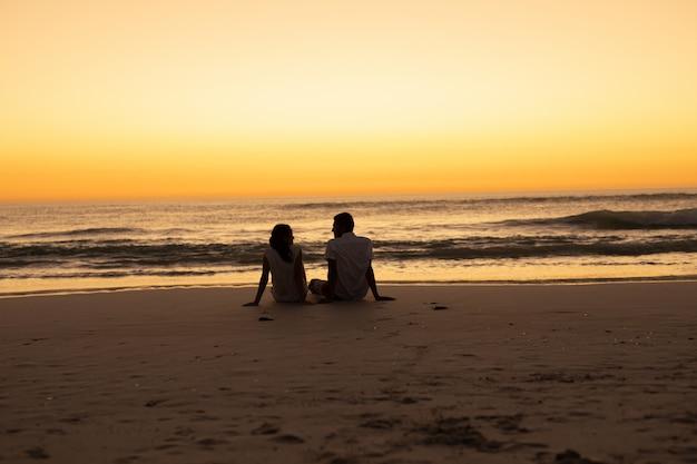 Paare, die auf den strand während des sonnenuntergangs aufeinander einwirken
