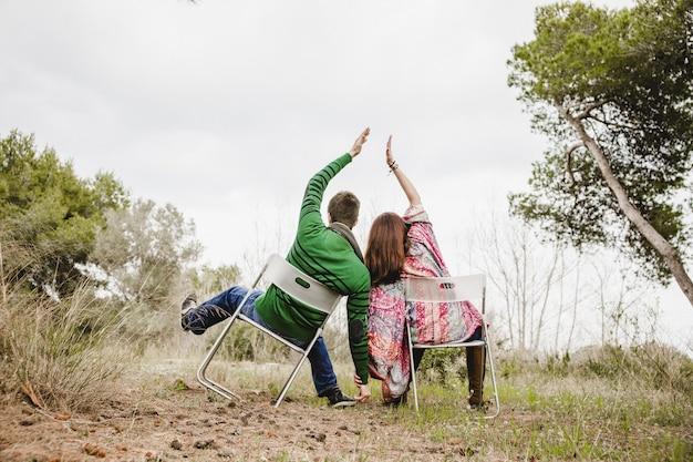 Paare, die auf den stühlen zusammen setzen ihre hände sitzen