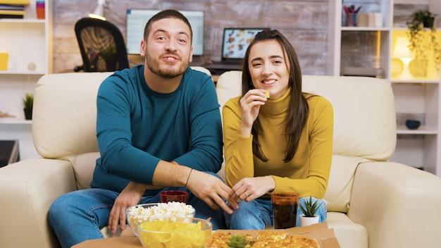 Paare, die auf der couch sitzen und lachen, während sie fernsehen und pizza essen. popcorn und pizza auf dem couchtisch.