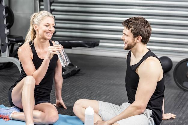 Paare, die auf eignungsmatte an crossfit turnhalle sitzen