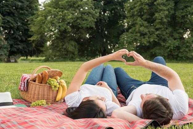 Paare, die auf eine picknickdecke legen