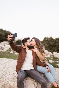 Paare, die auf einem felsen bleiben und ein selfie nehmen