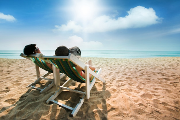 Paare, die auf einem strandstuhl und -regenschirm ein sonnenbad nehmen