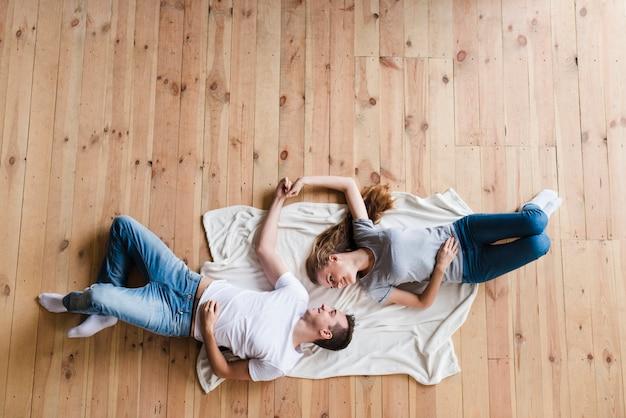 Paare, die auf fußboden liegen und hände anhalten
