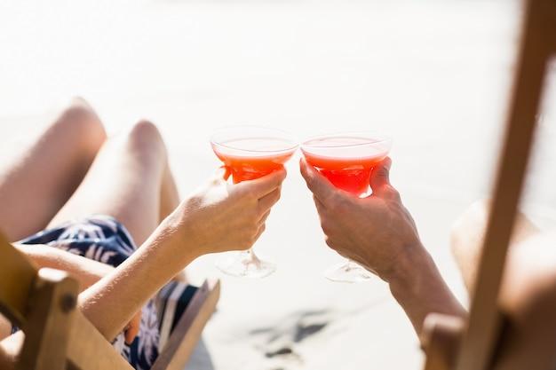 Paare, die auf lehnsessel mit cocktailgetränk sitzen