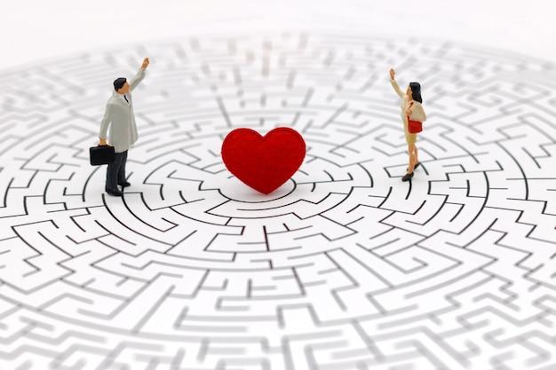 Paare, die auf mitte des labyrinths mit rotem herzen stehen.