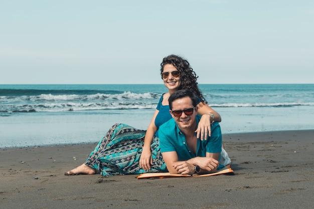 Paare, die auf sandigem strand stillstehen