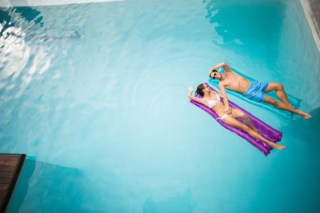 Paare, die auf schlauchboot am swimmingpool sich entspannen