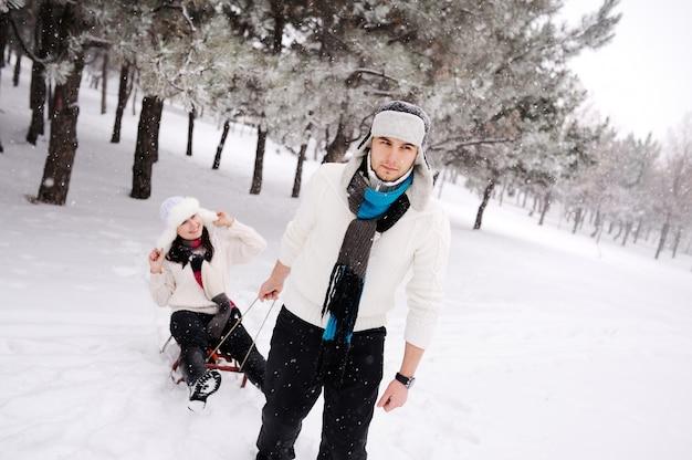 Paare, die auf schneebedecktem feld rodeln