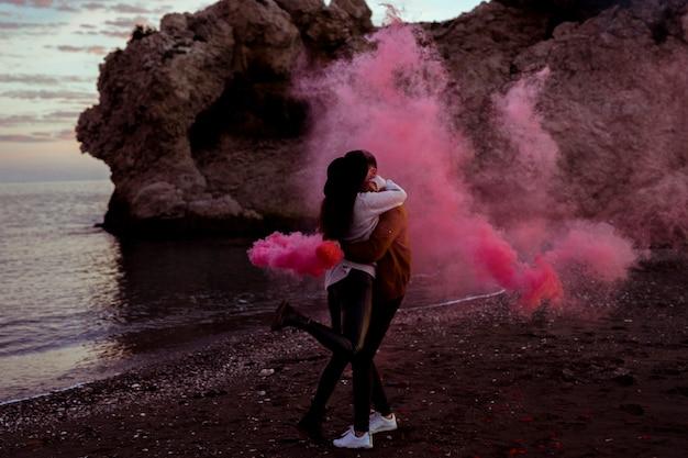 Paare, die auf seeufer mit rosa rauchbombe umarmen