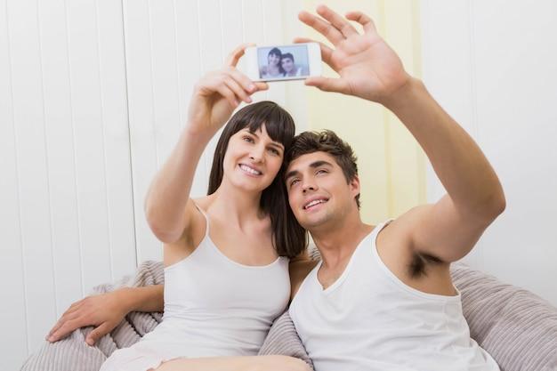 Paare, die auf sofa liegen und ein selfie am handy nehmen