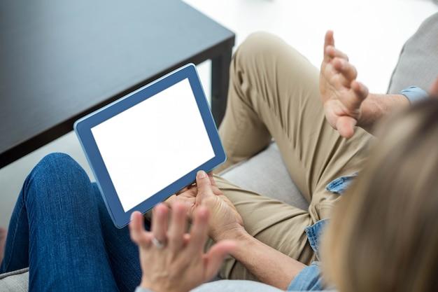 Paare, die auf sofa sitzen und digitale tablette verwenden