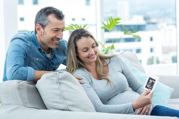 Paare, die auf sofa sitzen und ultraschallscan betrachten