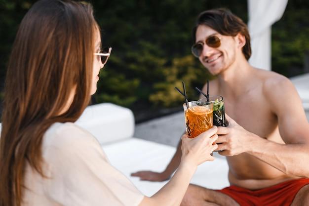 Paare, die auf sonnenruhesessel am strand sich entspannen