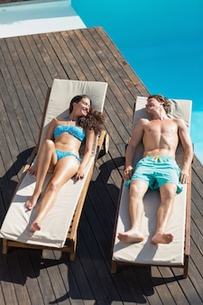 Paare, die auf sonnenruhesesseln durch swimmingpool stillstehen