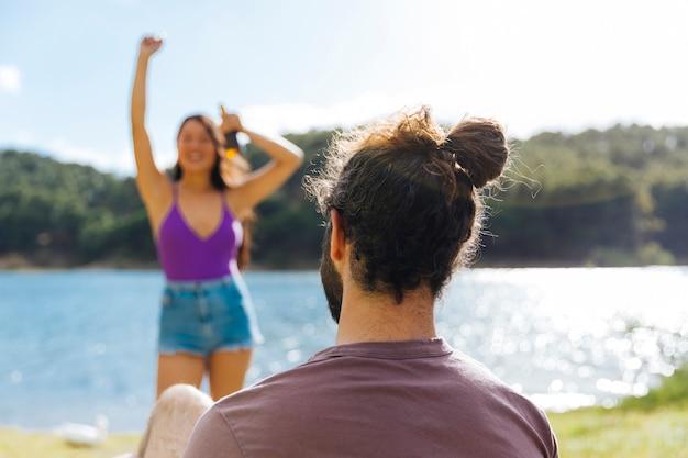 Paare, die auf sonnigem flussufer stillstehen