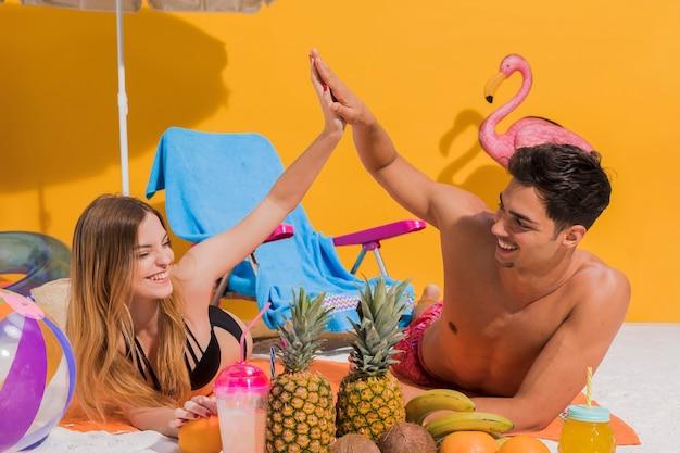 Paare, die auf strand mit früchten stillstehen