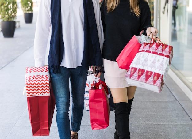 Paare, die auf straße mit einkaufstaschen gehen