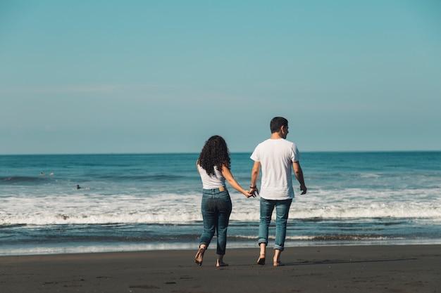 Paare, die barfuß auf sand zum meer gehen