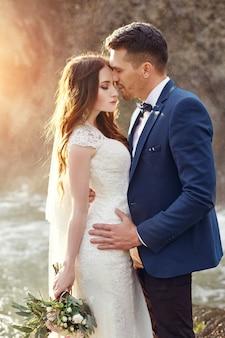 Paare, die bei sonnenuntergang, liebespaarküssen umarmen