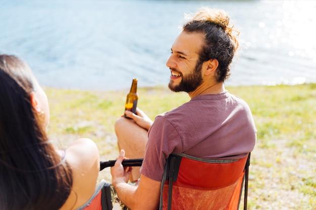 Paare, die beim bier auf flussufer liegen