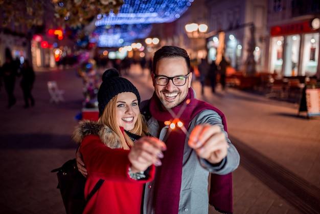 Paare, die bengal-lichter in der stadtstraße halten. lächeln und blick in die kamera.