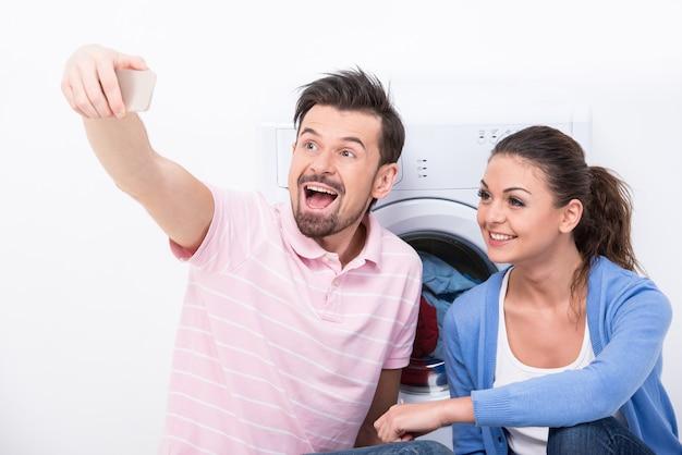 Paare, die bilder beim sitzen nahe waschmaschine machen.