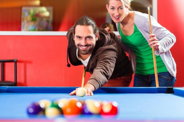 Paare, die billardspiel spielen
