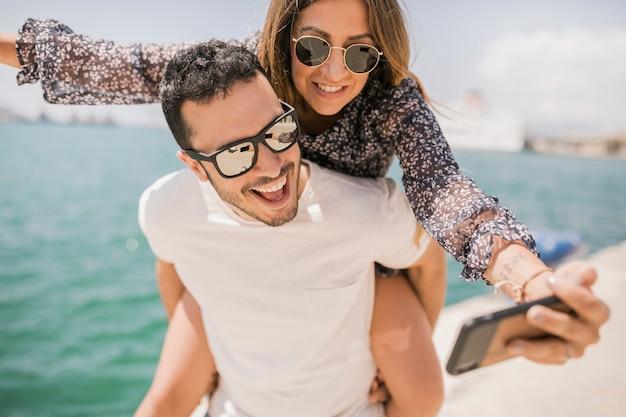 Paare, die das nehmen des selbstporträts am handy genießen