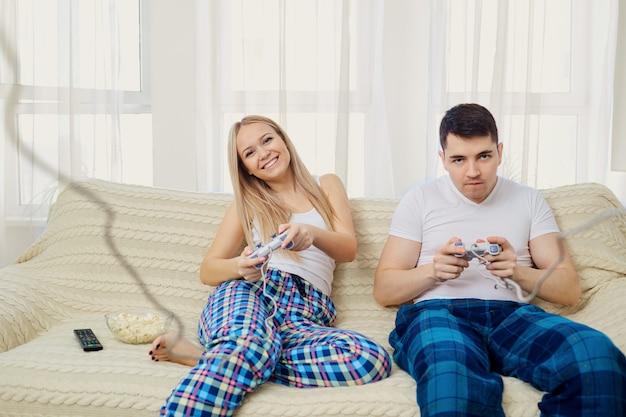 Paare, die das videospiel sitzt auf sofa im raum spielen