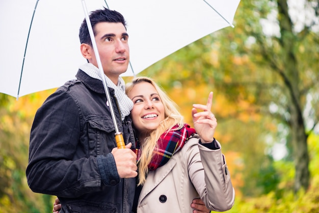 Paare, die den herbsttag trotz des regens spazieren genießen