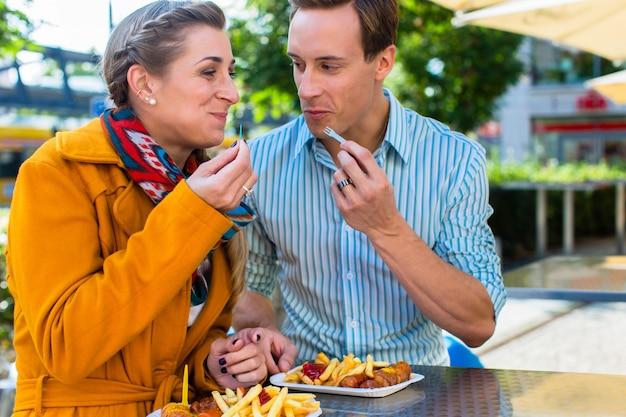 Paare, die deutsche currywurst am stand essen