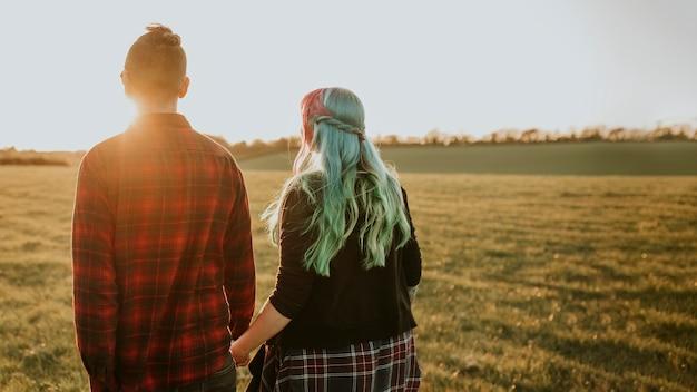 Paare, die draußen gehen und händchen halten