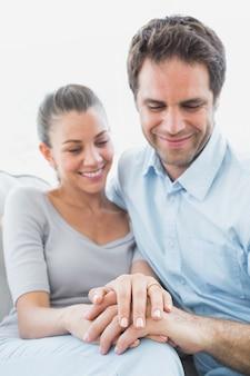 Paare, die ehering auf dem finger der frau auf der couch betrachten