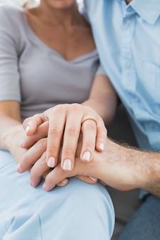 Paare, die ehering auf dem finger der frau auf der couch zeigen